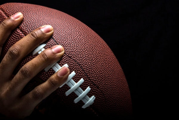 NFL player grips a football after sanitizing his hands.